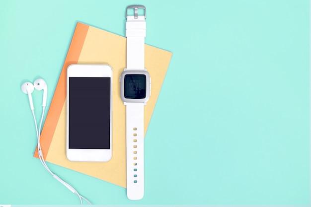Svuoti il telefono cellulare con i gadget dello smartwatch sul blu