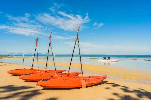Svuoti la barca o la nave del kajak sulla spiaggia e sul mare tropicali