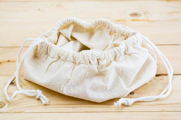 Svuoti la borsa aperta della tela sui legami per alimento su una tavola di legno naturale. concetto di rifiuti zero