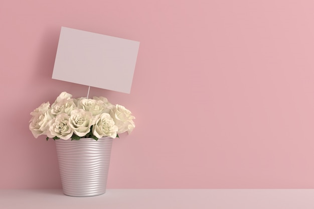 Svuoti la carta in bianco con la rosa di bianco in una stanza rosa