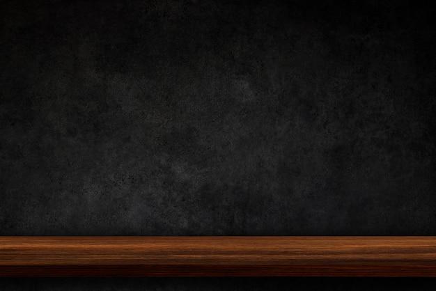Svuoti la cima degli scaffali di legno sul fondo scuro del muro di cemento
