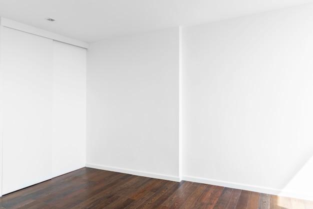 Svuoti la parete bianca nella sala con il pavimento di legno.
