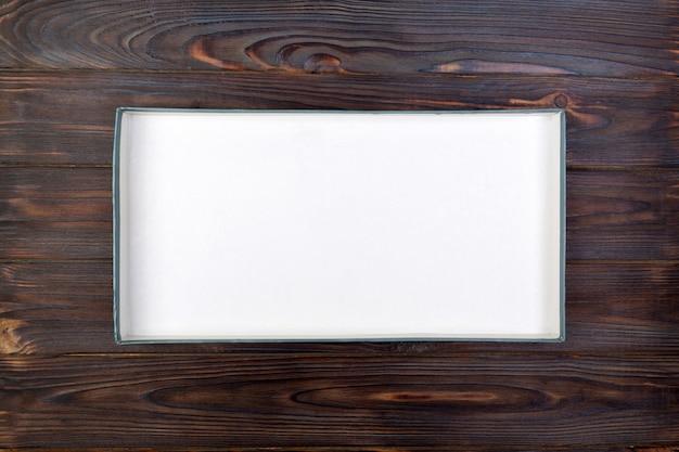 Svuoti la scatola di cartone bianca aperta per derisione sulla tavola di legno scura con lo spazio della copia