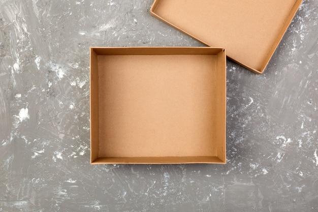 Svuoti la scatola di cartone marrone aperta per derisione sulla tavola grigia del cemento con lo spazio della copia