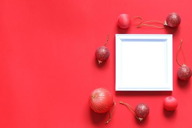 Svuoti la struttura nera della foto e la decorazione di natale su fondo rosso.