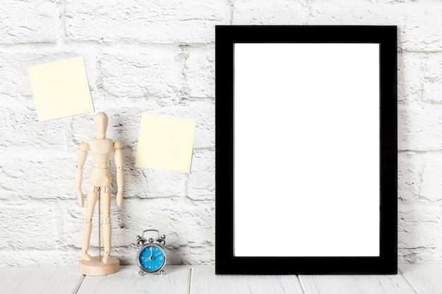 Svuoti la struttura nera della foto sullo scaffale o sul tavolo di legno. mockup con copia spazio.