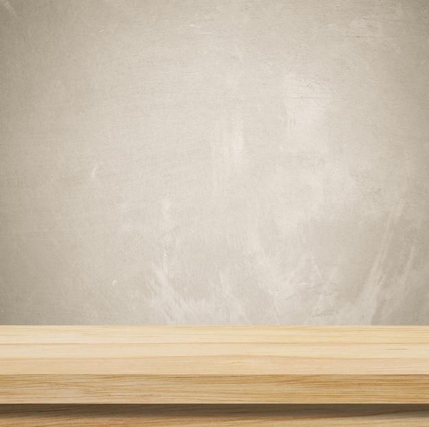 Svuoti la tabella di legno sopra la priorità bassa della parete del cemento del grunge