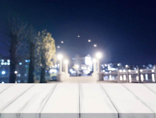 Svuoti la tavola bianca di legno davanti alle luci vaghe della città alla notte