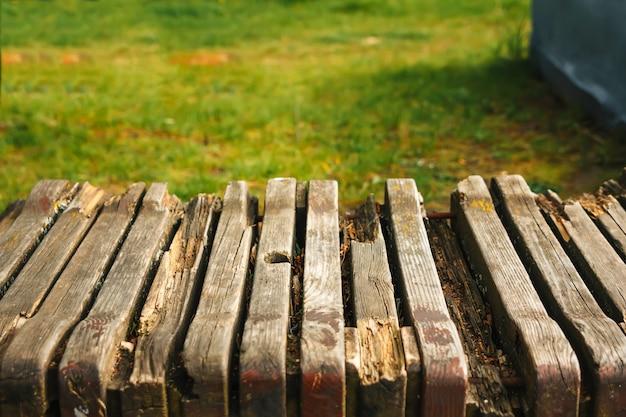Svuoti la tavola di legno con il bokeh del giardino per un approvvigionamento o l'alimento con un tema all'aperto del paese, modello derisione su per l'esposizione del prodotto