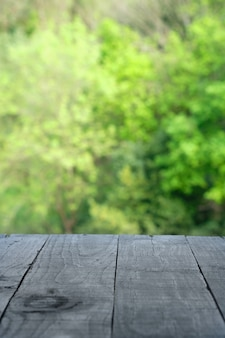 Svuoti la tavola di legno con l'area del giardino per un pasto o un fondo dell'alimento con un tema all'aperto del paese