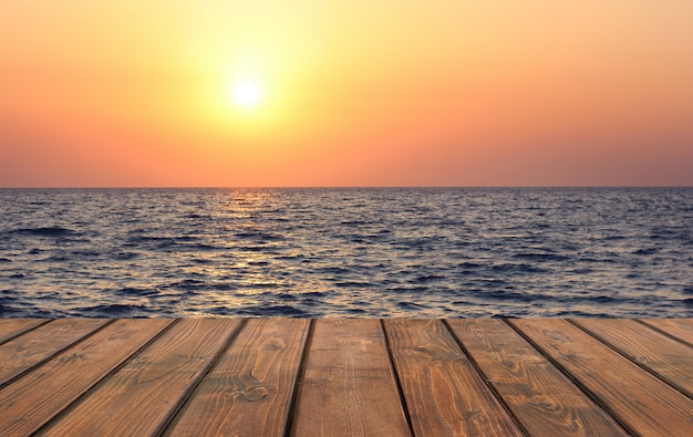 Svuoti la tavola di legno contro il tramonto sul mare.