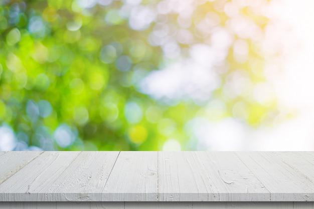 Svuoti la tavola di legno e il bokeh verde vago estratto lascia la struttura del fondo, montaggio dell'esposizione con lo spazio della copia.