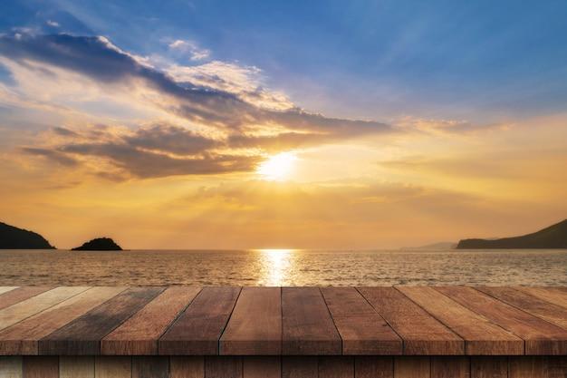 Svuoti la tavola di legno e il paesaggio del tramonto sul mare della costa, onde con il montaggio dell'esposizione per il prodotto.