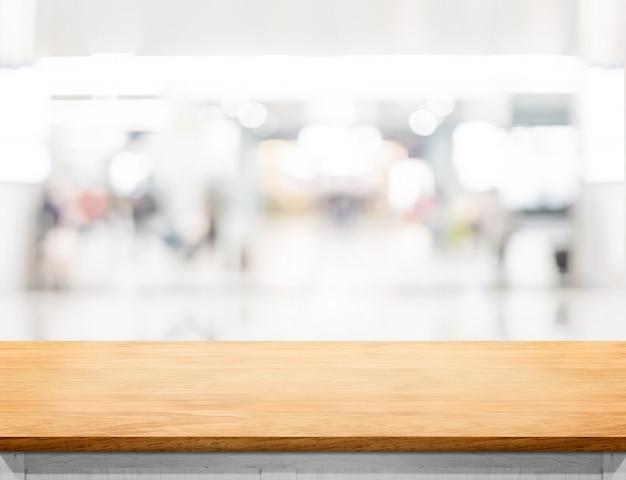 Svuoti la tavola di legno ed il fondo vago della luce del bokeh del centro commerciale di acquisto