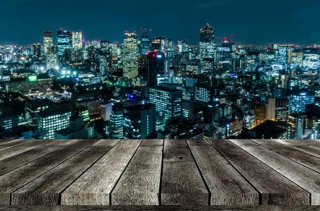 Svuoti la tavola di legno grigia o il terrazzo di legno con l'immagine vaga di paesaggio urbano di notte dal fondo del distretto aziendale