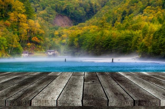Svuoti la tavola di legno grigia o il terrazzo di legno con la bella vista dello stagno di taisho al parco nazionale di kamikochi nelle alpi del nord del giappone