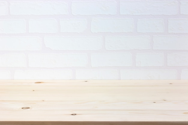 Svuoti la tavola di legno sopra il muro di mattoni bianco, modello