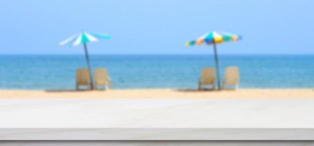 Svuoti la tavola di marmo bianca sopra il cielo blu della sfuocatura e la spiaggia del mare con l'ombrello variopinto