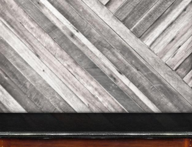 Svuoti la tavola di marmo nera e la parete di legno della plancia diagonale vaga nel fondo