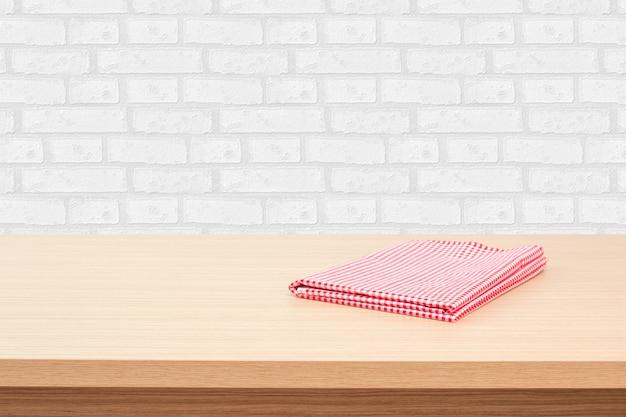 Svuoti la tavola di piattaforma di legno con la tovaglia sopra il fondo bianco della carta da parati del mattone. perfetto per la visualizzazione del montaggio del prodotto