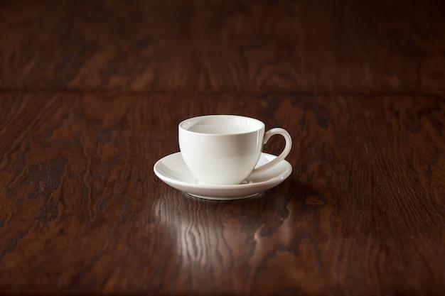 Svuoti la tazza bianca elegante sulla tavola di legno scura