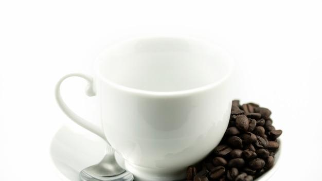 Svuoti la tazza di caffè macchiato con i chicchi di caffè isolati su fondo bianco
