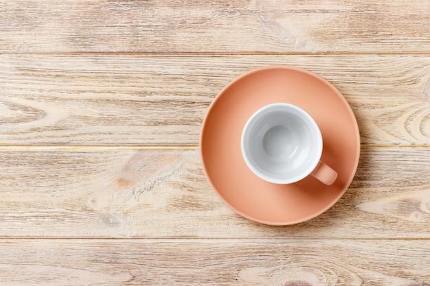 Svuoti la tazza variopinta sul piatto per caffè o tè, vista superiore