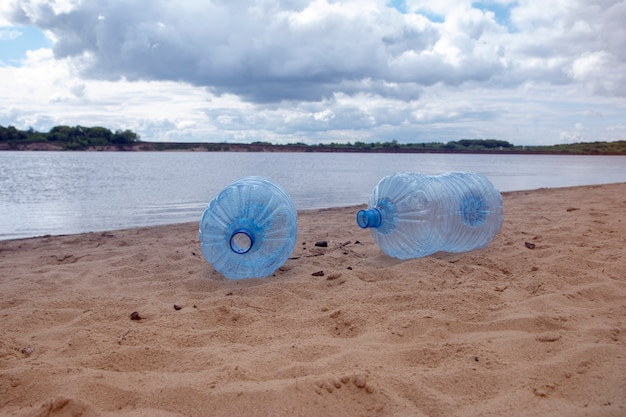 Svuoti le bottiglie di plastica sporche utilizzate. riva sabbiosa del fiume sporco. inquinamento ambientale. problema ecologico.