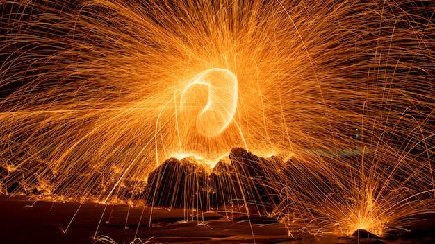 Swing fire agitare la fotografia leggera di lana d'acciaio con il riflesso nello stile di movimento della velocità di esposizione lunga dell'acqua