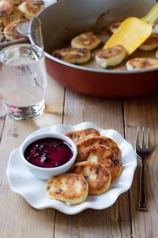 Syrniki russo tradizionale con uvetta. frittelle di quark dolci con salsa di mirtilli