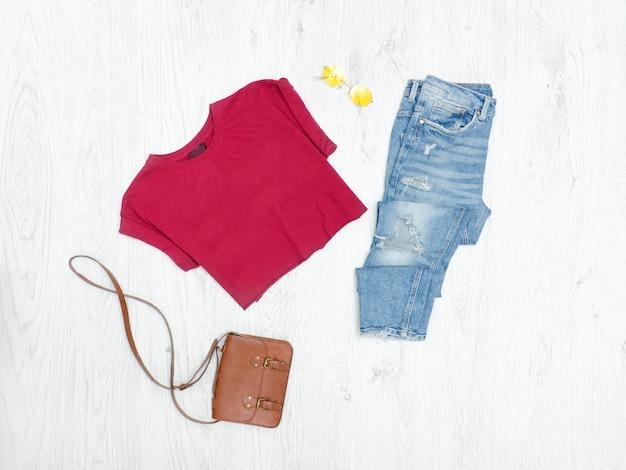T-shirt bordeaux, jeans strappati, borsa e occhiali da sole. concetto alla moda