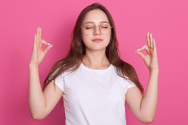 T-shirt casual bianca bellissima da donna che medita con gli occhi chiusi, rilassa il corpo e schiarisce la mente