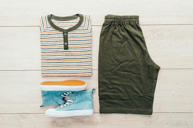 T-shirt con pantaloni e scarpe su sfondo in legno