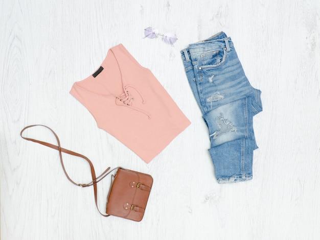 T-shirt rosa, jeans strappati, borsa e occhiali da sole. concetto alla moda