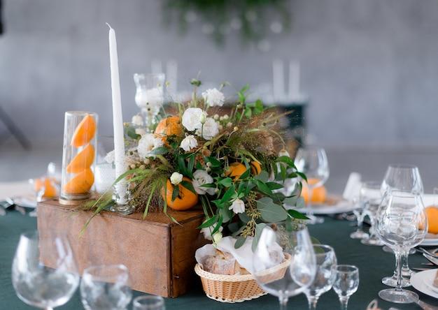 Tabella che serve con composizione floreale con arance sul tavolo verde nel ristorante