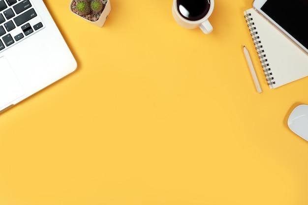Tabella dell'area di lavoro con computer e articoli per ufficio su giallo