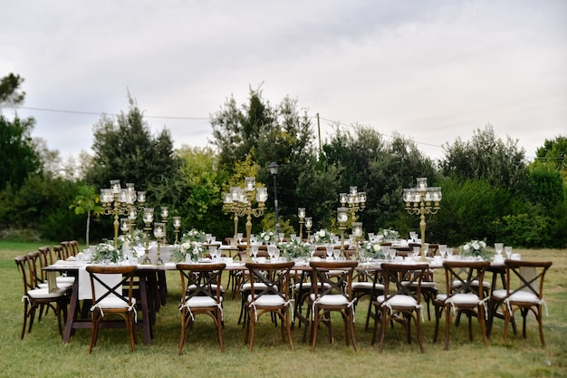 Tabella di celebrazione di cerimonia nuziale decorata con posti a sedere per gli ospiti all'aperto nei giardini