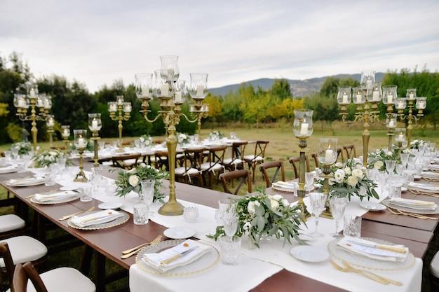Tabella di celebrazione di cerimonia nuziale decorata con sedili ospiti all'aperto nei giardini con vista sulle montagne