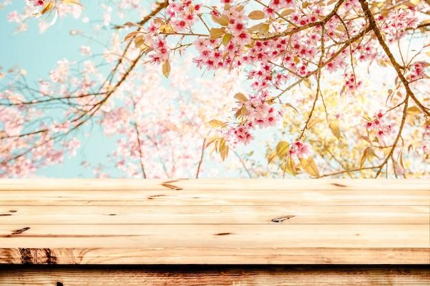 Tabella di legno superiore con fiore di ciliegio rosa (sakura) sullo sfondo del cielo in stagione primaverile - vuoto pronto per il tuo prodotto e cibo display o montaggio. tono di colore dell'annata.