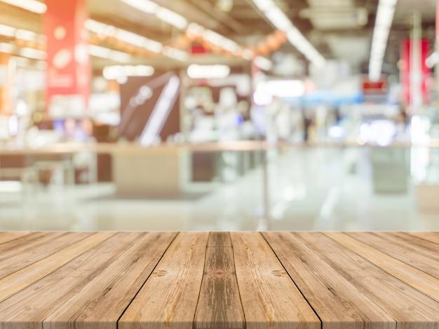 Tabella di legno tabella vuota offuscata priorità bassa. prospettiva legno marrone sopra sfocatura nel grande magazzino - può essere utilizzato per la visualizzazione o il montaggio dei vostri prodotti.cassa per la visualizzazione del prodotto.