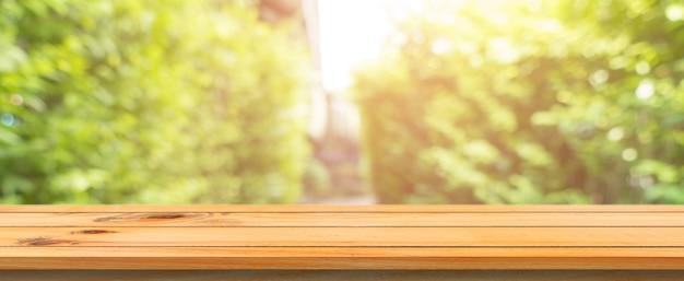Tabella di legno tabella vuota offuscata priorità bassa. prospettiva tavolo di legno marrone su sfondi foresta sfondo sfocato - può essere utilizzato mock up per visualizzare o montare i tuoi prodotti. stagione primaverile. banner panoramico.