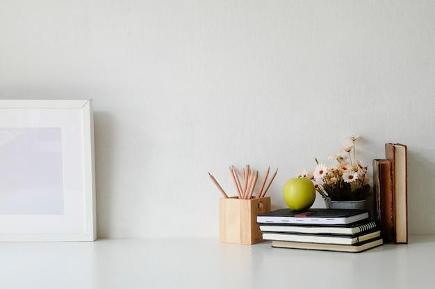 Tabella di mockup con fiore, cornice per foto, libri, mela verde e vaso di matita sul tavolo bianco.