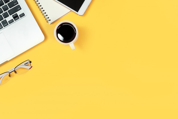 Tabella di woking con il computer portatile su giallo