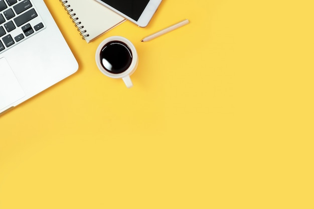 Tabella e computer portatile dell'area di lavoro su giallo
