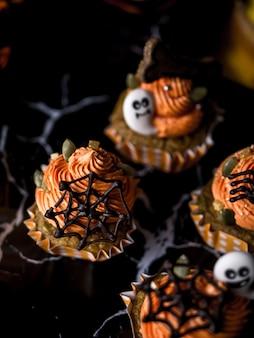 Tabella operata del partito dell'alimento di halloween con il muffin e i biscotti del bigné della zucca.