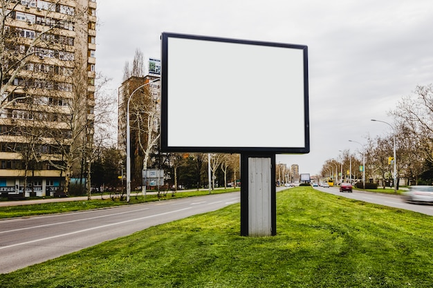 Tabellone per le affissioni della città in bianco del bordo della strada in mezzo alla strada
