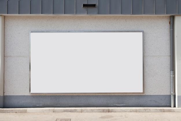 Tabellone per le affissioni di pubblicità in bianco sul muro di cemento