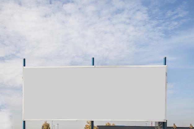 Tabellone per le affissioni in bianco con lo spazio della copia per il messaggio di testo o il contenuto contro il cielo