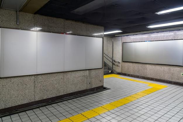 Tabellone per le affissioni in bianco situato nel corridoio sotterraneo o metropolitana per la pubblicità, concetto di mockup