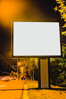Tabellone per le affissioni in bianco sul bordo della strada della città alla notte